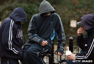 Young people with hooded tops drinking in public place