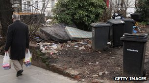 Pedestrian walks past rubbish in someone's front garden