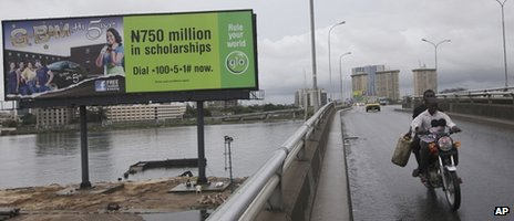 A man ride on a motor taxi past a giant advertisement bill board for Glo Nigeria, a Globacom company, in Lagos, Nigeria -Sunday 13 May 2012