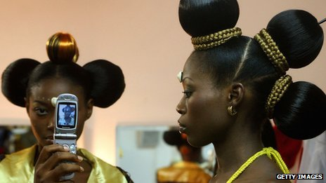 Nigerian fashion models, one holding up a mobile phone