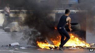 Man standing by burning tyre in Beirut street, 22 May 2012