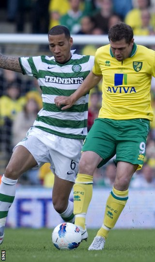 Kelvin Wilson challenges Norwich striker Grant Holt at Carrow Road