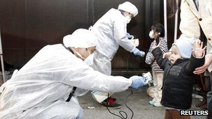 Officials in protective gear check for signs of radiation on children who are from the evacuation area near the Fukushima Daiichi nuclear plant in Koriyama, March 13, 2011.