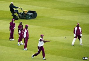 Groundsman at Lords cricket ground tends the grass as west Indies players warm up for a match