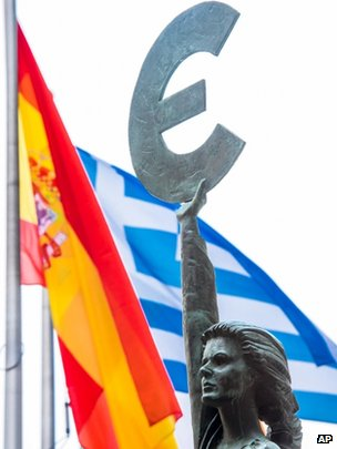 The flags of Spain and Greece wave behind a statue holding the symbol of the euro