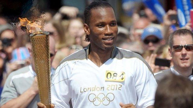 Didier Drogba runs with the Olympic torch along Market Street in Swindon, Wiltshire