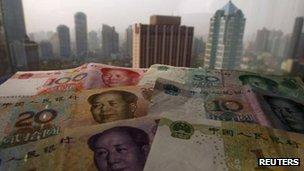China yuan bank notes and the Shanghai skyline