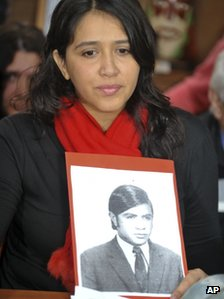 Victoria Montenegro holds a photograph of her father