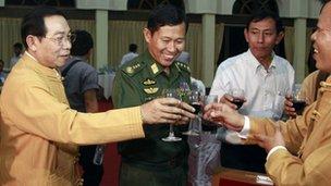 Negotiators hold up glasses of wine.
