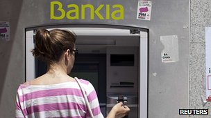 A woman withdraws cash from a bank in Spain
