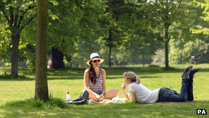 Two women relax in the sunshine in Hyde Park in London