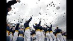 Graduates of US Air Force class 2012 throw their hats in the air as fighter jets fly past