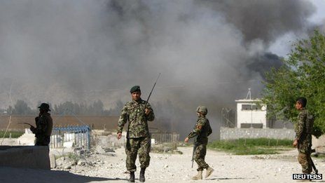 Soldiers from the Afghan National Army keep watch near the Provincial Reconstruction Team (PRT) as smoke rises from the site of an attack in Jalalabad province April 15, 2012.
