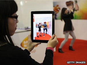 Woman uses Aurasma app on an iPad which displays a virtual 3D animation of a Thundercat character