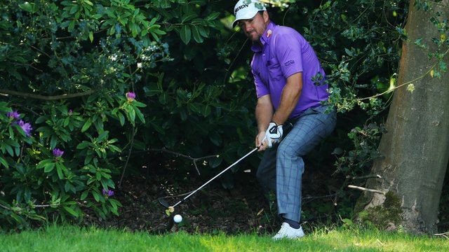 Graeme McDowell plays his ball out of the trees