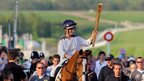 Zara Phillips carrying the Olympic flame on horseback at the end of day five at Cheltenham Racecourse.