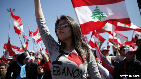 Protesters wave Lebanese flags during a demonstration in Beirut on the anniversary of a popular uprising.