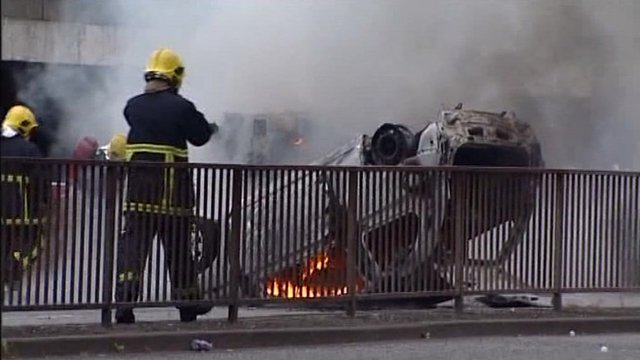 Firemen next to a burning upturned car