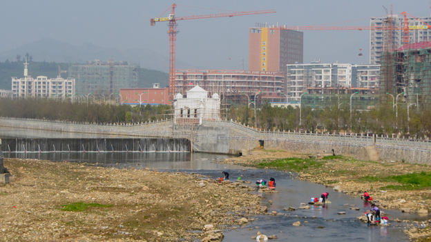 Women washing clothes in river against backdrop of new apartment blocks