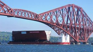 Part of carrier sails under Forth Bridge