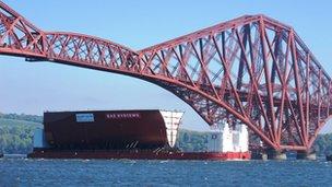 Part of carrier sails under Forth Bridge