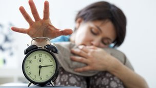 Tired woman switching off alarm