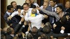 Men scuffle during a session in the chamber of the Ukrainian parliament in Kiev