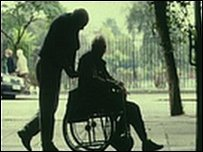 person in a wheelchair and helper
