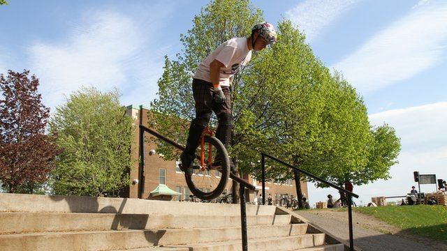Hugo Duguay going down a rail on a unicycle