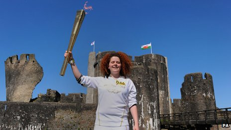 Bronwen Davies holds the torch aloft at Caerphilly Castle