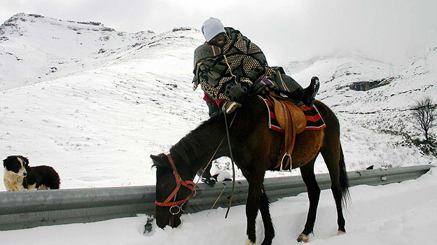 Basotho mounts horse in snow-covered mountains