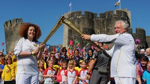 Two torchbearers in a &quot;kiss&quot; handover outside Caerphilly Castle 