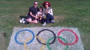 Jeremy, Wenda and Augsta with an Olympic torch in Mumbles, Swansea.