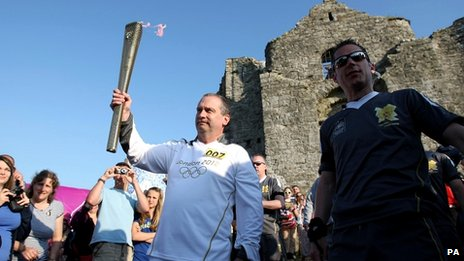 A torchbearer holds the flame aloft at Oystermouth Castle