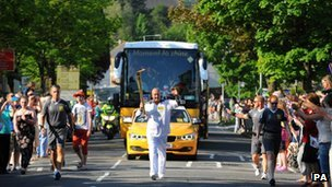 Torchbearer Peter Barnes carries the torch in Swansea