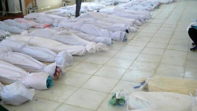 Bodies lying at a hospital morgue before their burial in the central Syrian town of Houla