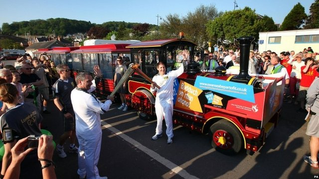 Philip Richards (left) passes the Olympic flame to Paul Adams in Mumbles, Swansea