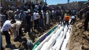 People gather at a mass burial for the victims purportedly killed during an artillery barrage from Syrian forces in Houla in this handout image dated May 26, 2012