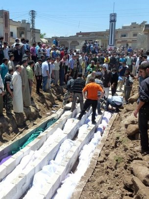 People gather at a mass burial for the victims purportedly killed by Syrian forces in Houla