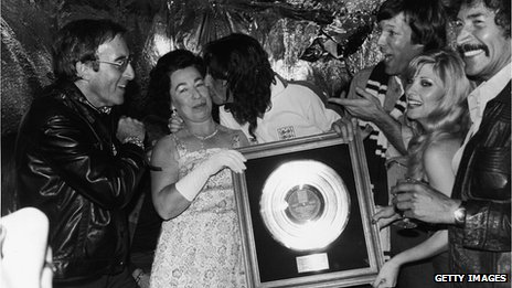 American rock singer Alice Cooper kisses Queen Elizabeth II impersonator Jeannette Charles while holding his gold record plaque as left to right actors Peter Sellers, Richard Chamberlain, Lyn de Paul and Peter Wyngarde look on, 1975. Photo by Express Newspapers/Getty Images