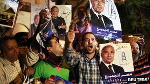 Supporters of candidate Ahmed Shafiq hold his pictures as they celebrate in Cairo on Friday evening