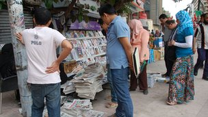 Men and women read newspapers at a newspaper stall on a Cairo pavement close to Tahrir Square.