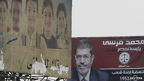 An election campaign poster for Muslim Brotherhood candidate Mohammed Mursi, near an offical election poster encouraging people to vote for the sake of Egypt&#039;s future.