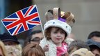 A young girl wears a homemade crown as she waits to see Queen Elizabeth II visit the town centre of Accrington as part of the Queen&#039;s Diamond Jubilee tour of the country on 16 May 2012