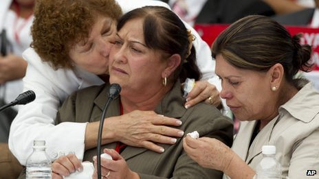 Maria Gonzalez , centre, mother of two missing children is comforted by other relatives of victims of drug gang-related violence during the meeting at the Chapultepec Castle in Mexico City