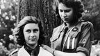 Britain's Queen Elizabeth II, then Princess Elizabeth, right, and Princess Margaret, in their Girl Guide uniforms, practice their bandaging skills in this August 1943 file photo. Princess Elizabeth is wearing the badge of the swallow patrol and two white stripes, which indicates that she is patrol leader.