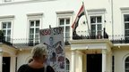 A protester stands outside the Syrian embassy in London with a placard depicting Syrian President Bashar al-Assad as a killer, 29 May