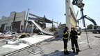 Italian firefighters search the debris of a collapsed factory in Mirandola, northern Italy, on Tuesday