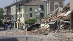 People walk past a building in Cavezzo, Italy, which collapsed in Tuesday morning's earthquake