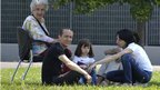 People evacuated from their homes sit on the grass in Mirandola, northern Italy, Tuesday following the earthquake